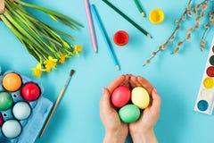 La vue supérieure de Pâques sur le lieu de travail bleu de bureau de table Photo stock