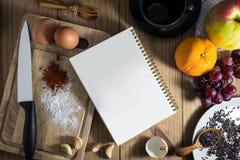 La vue supérieure de préparent la cuisson : carnet et oeufs blancs, couteau, assaisonnant sur le hachoir et tasse de thé, fruit,  Photographie stock libre de droits