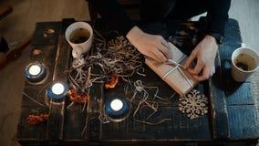 La vue supérieure de la séance femelle à la table avec décorer le personnel et faire le présent, attachent une boîte de Noël avec banque de vidéos