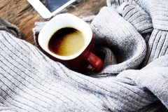 La vue supérieure de la tasse de café sur le gris a tricoté le chandail - table en bois - verre rouge Photo libre de droits