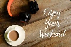 La vue supérieure des écouteurs et une tasse de café sur le fond en bois écrit avec APPRÉCIENT VOTRE WEEK-END images libres de droits