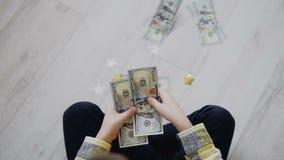 La vue supérieure des enfants remet tenir des dollars et les compter en les jetant sur le plancher à la maison Devise américaine clips vidéos