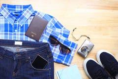 La vue supérieure des femmes façonnent les vêtements élégants des accessoires de voyage sur le fond en bois de table, prévoyant p photographie stock libre de droits