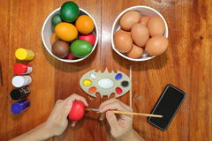 La vue supérieure des mains du jeune homme chrétien colore des oeufs de pâques avec un pinceau sur la table en bois photographie stock libre de droits