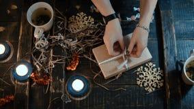 La vue supérieure des mains femelles lie une boîte avec un ruban, décorant le cadeau de Noël à l'ami s'asseyant à la table banque de vidéos