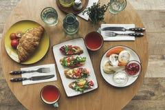 la vue supérieure des tasses de thé, des sandwichs et des gâteaux au fromage sur la table a servi images stock