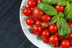 La vue supérieure des tomates-cerises et du basilic frais et organiques part sur un plat blanc et un tapis de table en bambou gri Photo libre de droits