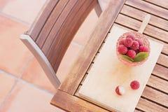La vue supérieure du beau bol en verre rose complètement avec des litchis portent des fruits et morceau de litchi épluché par moi Photographie stock libre de droits
