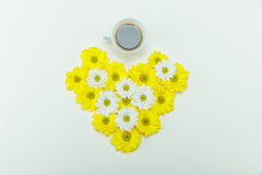 La vue supérieure du beau chrysanthème blanc et jaune fleurit dans la forme de coeur et la tasse de café Photos stock