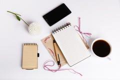 La vue supérieure du bloc-notes vide sur le bureau blanc avec le smartphone, bloc-notes, stylo, fleurissent la tasse blanche de d Photo stock