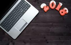 La vue supérieure du bureau de table de bureau avec l'ordinateur portable ouvert et la nouvelle année 2018 signent le symbole des Photo stock