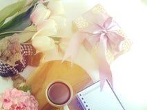 La vue supérieure du carnet de tasse de café de matin avec des fleurs et l'écharpe sur la copie espacent le fond blanc Photos libres de droits