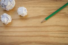 La vue supérieure du crayon vert avec des beaucoup blanc a chiffonné la boule de papier mise sur le plancher en bois Photo stock
