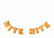 La vue supérieure du mot NITE NITE, faite avec l'alphabet a formé des biscuits sur le fond blanc, avec l'espace libre pour la con Photos stock