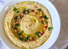 La vue supérieure du plat d'humus a garni avec les feuilles fraîches de persil, les morsures de poivrons rouges, les pois chiches photo libre de droits