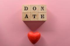 La vue supérieure en gros plan des cubes en bois avec le mot donnent et symbole rouge de coeur Image stock