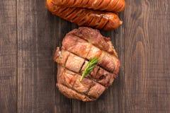La vue supérieure a grillé le bifteck et la saucisse sur un fond en bois images libres de droits