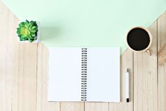 La vue supérieure ou la configuration plate du papier ouvert de carnet avec les pages vides et la tasse de café sur le fond en bo Image libre de droits