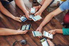 La vue supérieure remet le cercle utilisant le téléphone en café - scène intérieure dépendante de mobile multiracial d'amis de ci Photo libre de droits
