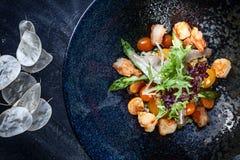 La vue sup?rieure sur la crevette, la tomate-cerise et la salade chaudes d'asperge a servi dans le plat fonc? sur le fond fonc? N image libre de droits