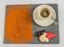 La vue supérieure sur le café dans une tasse porte des fruits et le mot délicieux Photos stock