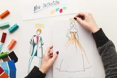 La vue supérieure sur le dessin de concepteur de femme vêtx des croquis Images stock