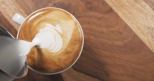 La vue supérieure versent le lait cuit à la vapeur dans le cappuccino sur la table en bois images libres de droits