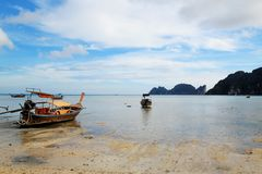 La vue sur les longs bateaux sur une côte de mer sur une marée basse Image libre de droits