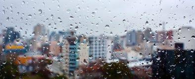La vue urbaine panoramique des baisses de pluie tombe sur une fenêtre photographie stock libre de droits