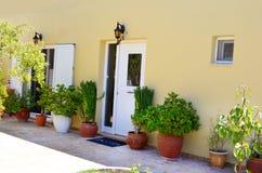 La yarda griega típica de una casa con las puertas blancas y el pote verde florece Fotos de archivo libres de regalías