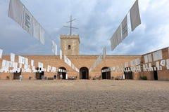 La yarda interna adornada con las banderas blancas y la torre del reloj de Montjuic se escudan, Barcelona, Cataluña, España Imágenes de archivo libres de regalías