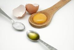 La yema de huevo en la cuchara, el aceite de oliva y la sal de madera en las cucharas y se rompió Imágenes de archivo libres de regalías
