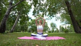 La yoga de la práctica de la mujer, se sienta en la actitud del loto, forma de vida sana, belleza interna almacen de video