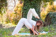 La yoga de los pares de la práctica del hombre joven y de la mujer presenta al aire libre en el día de verano de madera imagenes de archivo