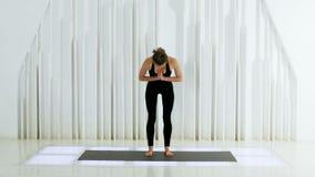 La yoga de la muchacha está haciendo un cabeceo y dobla sus manos en el pecho metrajes