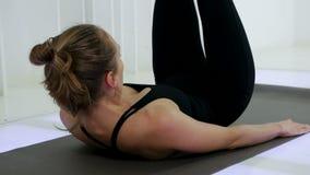 La yoga de la muchacha está mintiendo en la suya detrás almacen de video