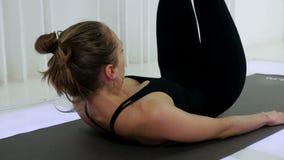 La yoga de la muchacha está mintiendo en la suya detrás almacen de metraje de vídeo