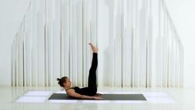 La yoga de la muchacha está mintiendo en la suya detrás metrajes