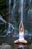 La yoga ejercita cerca de la cascada fotos de archivo libres de regalías