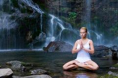 La yoga ejercita cerca de la cascada foto de archivo libre de regalías