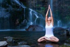 La yoga ejercita cerca de la cascada Fotografía de archivo libre de regalías
