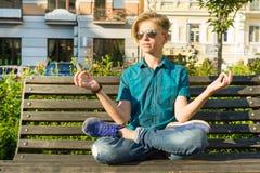 La yoga en la ciudad, adolescente se sienta en actitud del loto en banco en parque de la ciudad Relájese, descanse Fotos de archivo