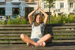 La yoga en la ciudad, adolescente se sienta en actitud del loto en banco en parque de la ciudad Relájese, descanse Imagen de archivo libre de regalías