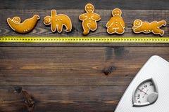 La yoga para pierde el peso Escala, cinta métrica y galletas en la forma de los asans de la yoga en la opinión superior del fondo Imagen de archivo