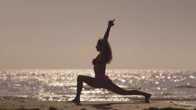 La yoga practic de la muchacha en la playa en la puesta del sol Chica joven que hace ejercicio en una playa tropical Silueta de u almacen de video