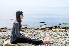 La yoga practicante de la muchacha en las rocas se coloca en una piedra Fotografía de archivo