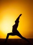 La yoga practicante de la mujer en la luz de la puesta del sol Imagen de archivo libre de regalías