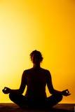 La yoga practicante de la mujer en la luz de la puesta del sol Foto de archivo