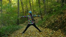 La yoga practicante de la mujer joven en otoño coloreó el bosque mientras que las hojas amarillas están cayendo alrededor de ella almacen de metraje de vídeo