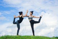 La yoga practicante de la mujer se relaja en fondo de la naturaleza y del cielo azul Foto de archivo libre de regalías